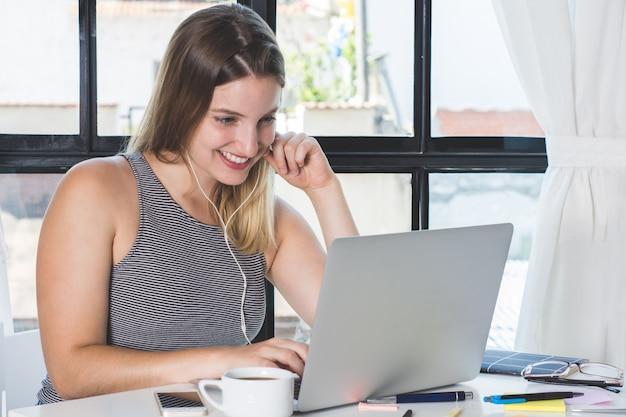 Frau, die zu hause an laptop arbeitet.