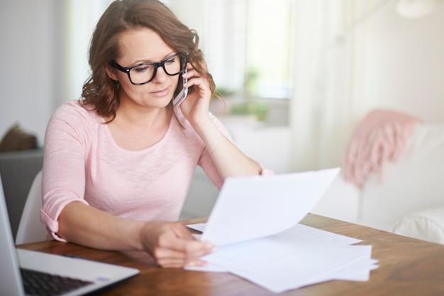 Frau, die zu hause arbeitet und am telefon anruft