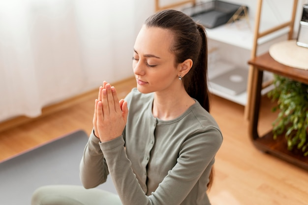 Frau, die zu hause auf matte meditiert