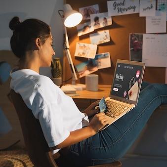 Frau, die zu hause auf schreibtisch des laptops schaut