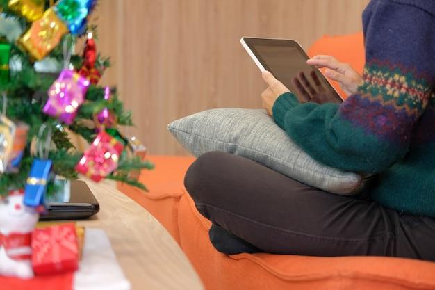 Frau, die zu hause auf sofa unter verwendung der tablette während weihnachten sitzt.