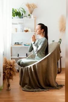 Frau, die zu hause auf stuhl meditiert