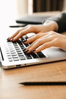 Frau, die zu hause büro arbeitet, hand auf der tastatur nah oben. frau, die zu hause mit laptop arbeitet, schreibt einen blog. weibliche hände auf der tastatur.