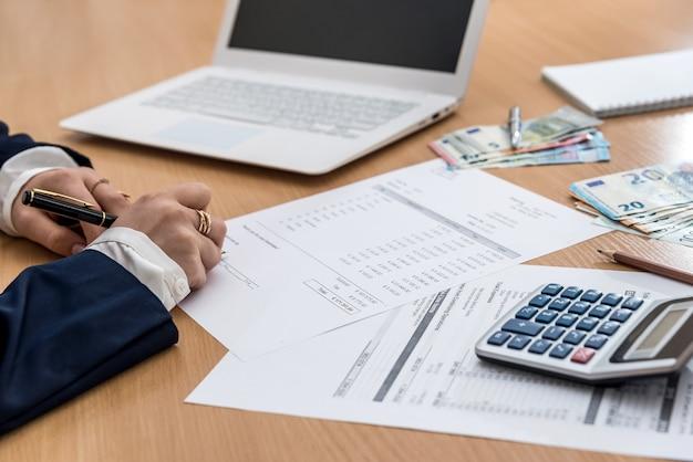 Frau, die zu hause buget mit laptop und konto euro-rechnung arbeitet