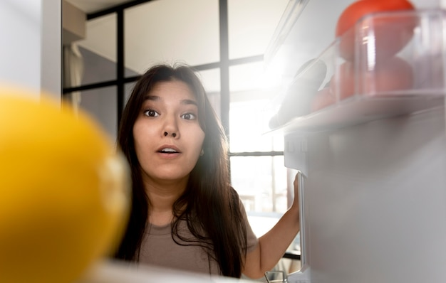 Frau, die zu hause das innere ihres kühlschranks überprüft