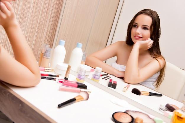 Frau, die zu hause das make-up sich vorbereitet für partei tut