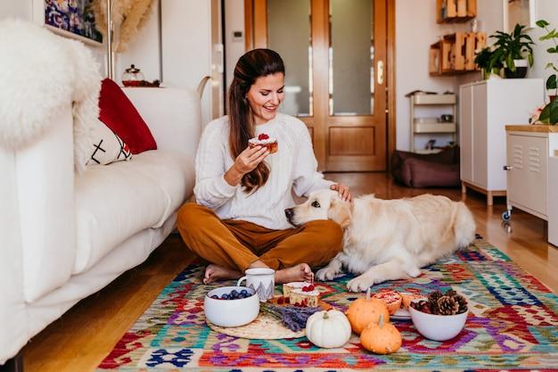 Frau, die zu hause ein stück bonbon während des frühstücks hält.