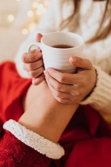 Frau, die zu hause entspannt und eine tasse tee hält