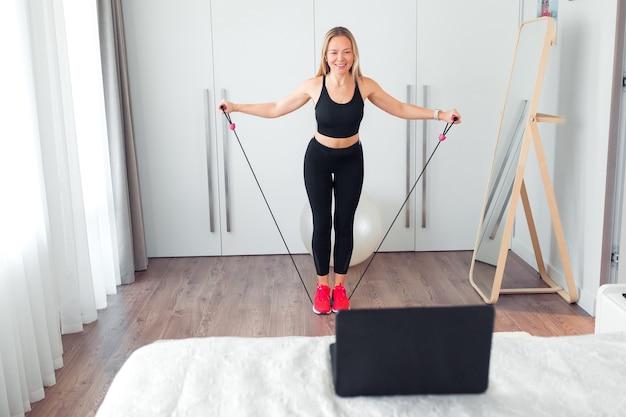 Frau, die zu hause fitnessübungen mit gummi für fitness macht