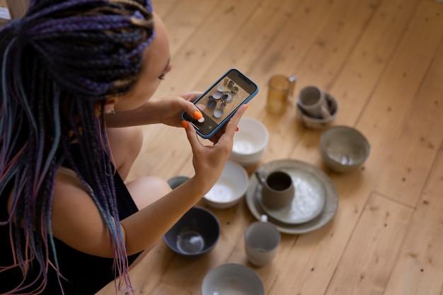 Frau, die zu hause fotos von keramikgeschirr macht