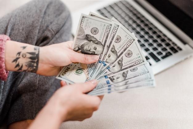 Frau, die zu hause geld auf einer couch mit laptop verdient