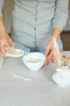 Frau, die zu hause gesundes frühstück zubereitet, weibliche hand, die eine flasche milch in müsli-müsliflocken-schüssel mit nusssamen-rosinen hält, hausmüsli-essen-hafer-mahlzeit, lifestyle-konzept