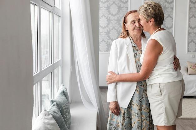 Frau, die zu hause ihre ältere mutter küsst