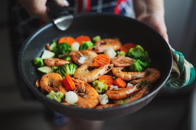 Frau, die zu hause in der küche bleibt und garnelen mit gemüse auf pfanne kocht. hausmannskost oder gesundes kochkonzept