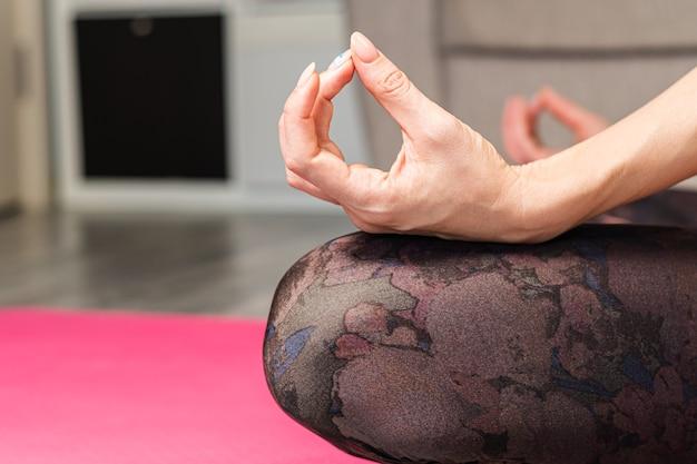 Frau, die zu hause in der lotusposition nahaufnahme meditiert. entspannung und meditation