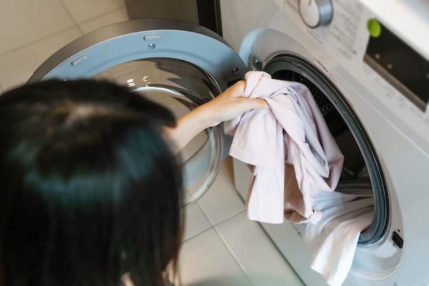 Frau, die zu hause kleidung in die waschmaschine in der küche steckt. wäschekonzept. nahaufnahme.