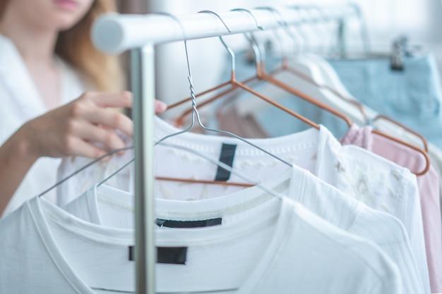 Frau, die zu hause kleidung kleiderschrank wählt