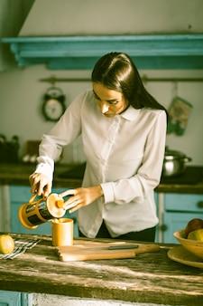 Frau, die zu hause küche im sonnigen morgen kocht