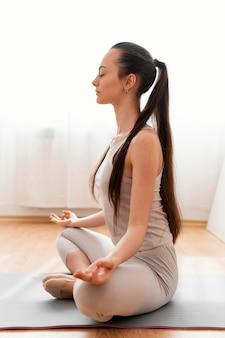 Frau, die zu hause meditiert