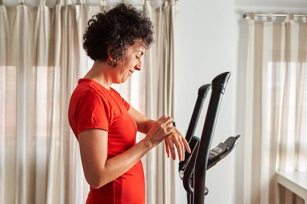 Frau, die zu hause mit dem ellipsentrainer trainiert, überprüft ihr smartband im wohnzimmer ihres hauses