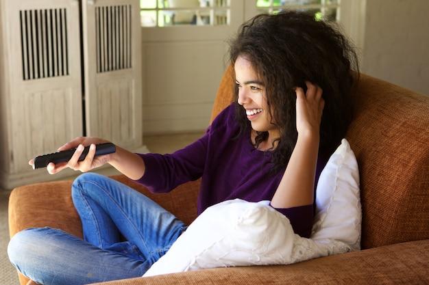 Frau, die zu hause mit der fernbedienung fernsieht sitzt