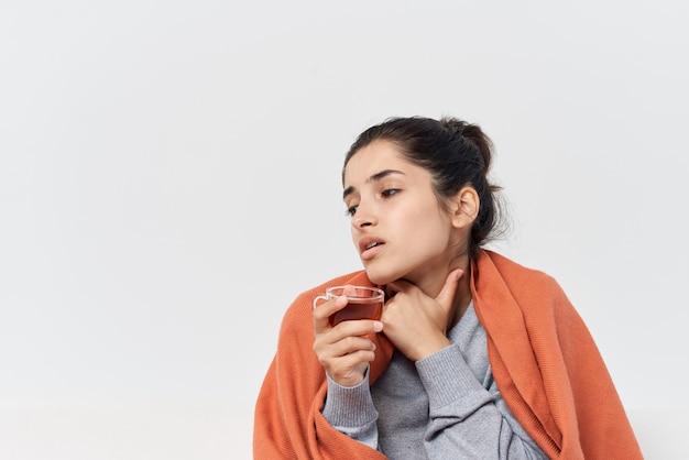 Frau, die zu hause mit einer decke bedeckt ist, trinkt tee gesundheitliche probleme