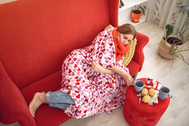 Frau, die zu hause mit einer kälte sitzt und heißen tee trinkt