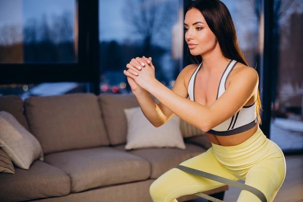 Frau, die zu hause mit gummiband trainiert