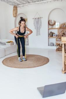 Frau, die zu hause mit gummiband trainiert.