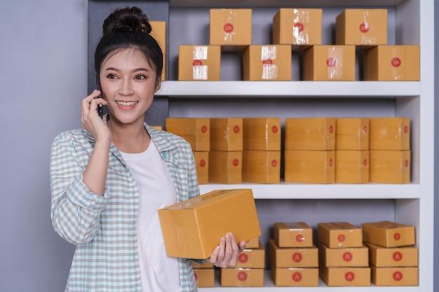 Frau, die zu hause mit ihrem büro des smartphone, kleiner onlinegeschäftseigentümer spricht