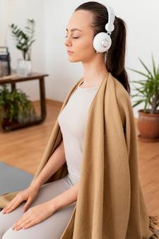 Frau, die zu hause mit kopfhörern meditiert