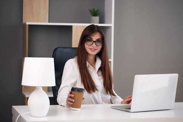 Frau, die zu hause mit laptop arbeitet und lächelt