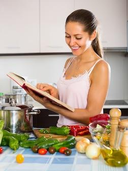 Frau, die zu hause mit veggies kocht