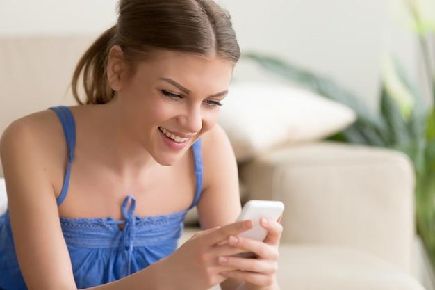 Frau, die zu hause mobile spiele auf mobiltelefon spielt