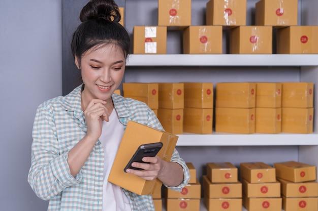 Frau, die zu hause produktbestellung mit büro des smartphone bearbeitet und überprüft