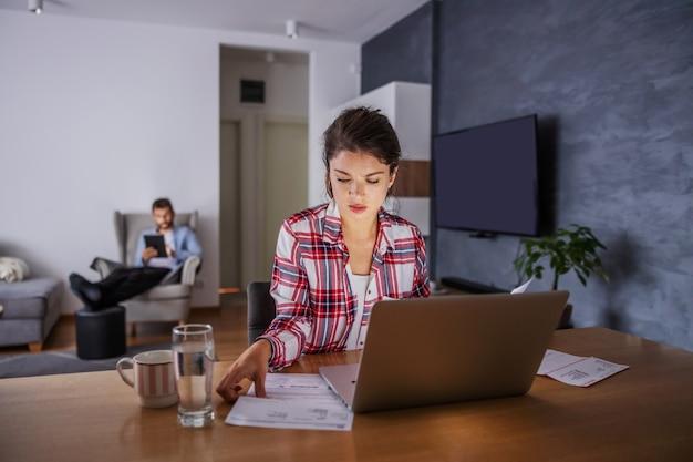 Frau, die zu hause sitzt und rechnungen online bezahlt. im hintergrund hängt ihr mann im internet.