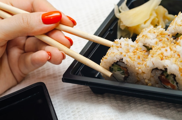 Frau, die zu hause sushi aus einem behälter mit japanischen stöcken isst.