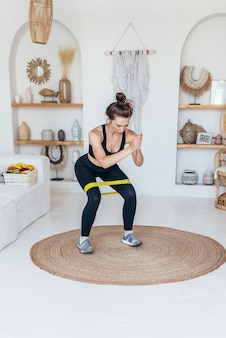 Frau, die zu hause trainiert und kniebeugen mit gummiband macht.