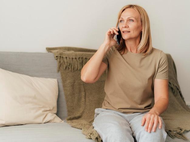 Frau, die zu hause während der quarantäne am telefon spricht