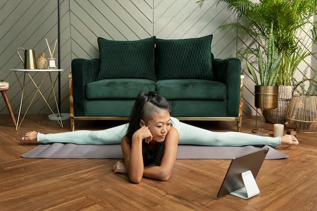 Frau, die zu hause yoga in der neuen normalität praktiziert