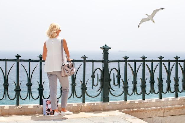 Frau, die zum meer im mittelmeerbalkon in tarragona schaut
