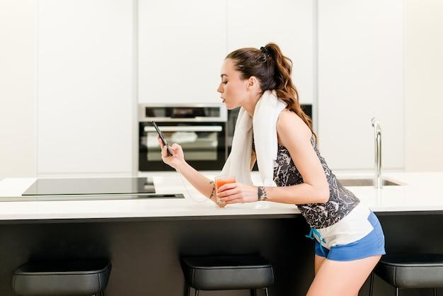 Frau, die zum training fertig wird, saft iand trinkt und ihr telefon betrachtet