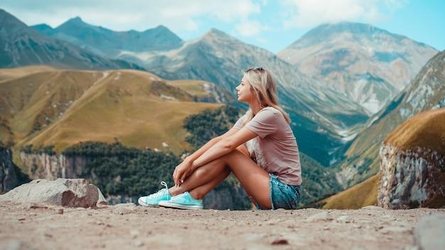 Frau, die zur sonnigen tageszeit in den bergen wandert ansicht von kazbegi, georgien