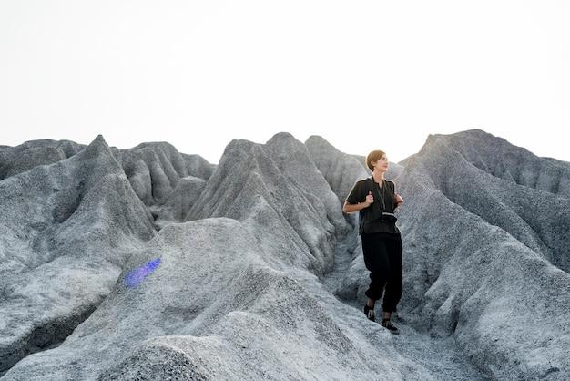 Frau, die zur spitze des berges in der natur wandert