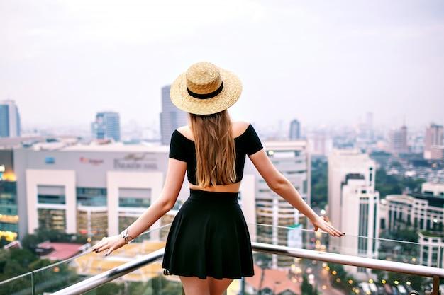 Frau, die zurück auf dach oben im luxushotel in bangkok aufwirft