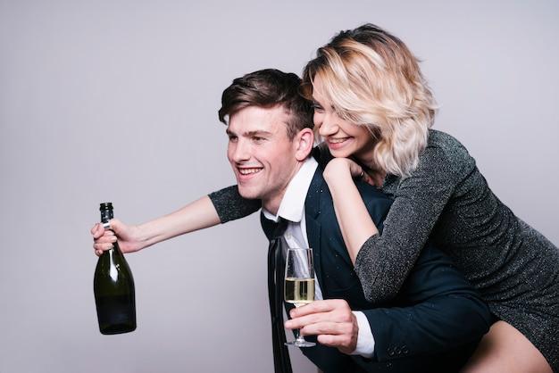Frau, die zurück auf mann mit champagnerflasche sitzt