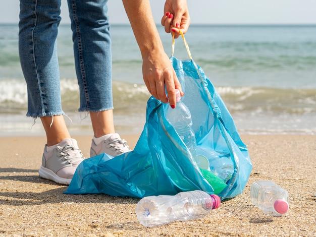 Frau, die zurückführbare plastikflasche im abfall sammelt