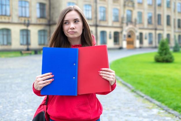 Frau, die zwei blaue und rote ordnercampusgebäude hält