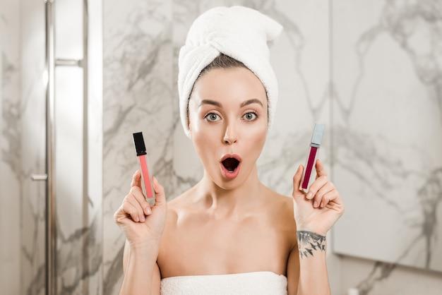 Frau, die zwischen den lippenstiften tun make-up im badezimmer nach dusche wählt