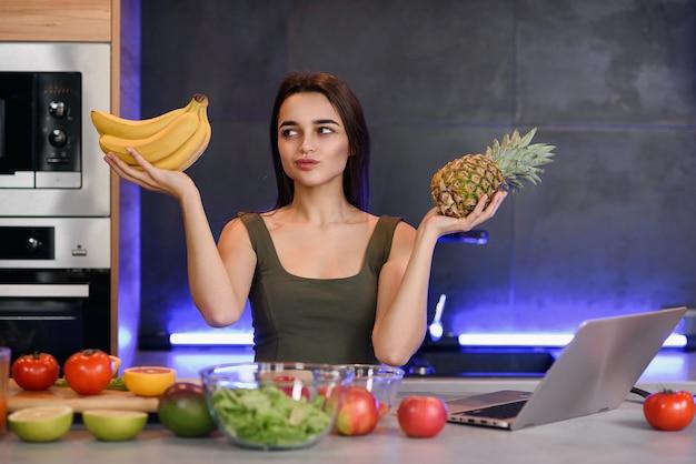 Frau, die zwischen nachtisch und früchten am tisch in der küche wählt. gesunde ernährung